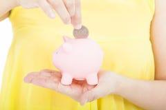 Hand för ung kvinna som sätter myntet in i piggy Royaltyfri Bild