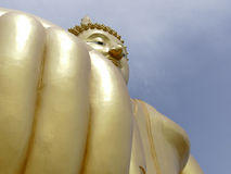 Hand and face of big golden buddha statue Stock Photo