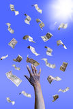 Hand with falling dollar banknotes. Hand with dollar banknotes falling from the sky Royalty Free Stock Photography