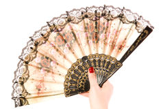 Hand with a fan. The female hand holds a beautiful fan opened on a white background closeup Stock Image