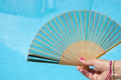 Hand fan in girls hand with clear blue water in background. Save Royalty Free Stock Photos