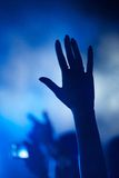 Hand of fan silhouetted against blue smoke Stock Photography