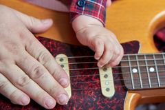The hand of the father and the child lies on a guitar. Dad teaches his son to play the guitar. Early child development. The hand of the father and the child lies stock photography