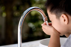 Hand and faucet Stock Image