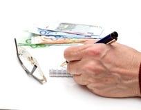 Hand, Feder, Notizbuch, Gläser und Geld Lizenzfreies Stockbild