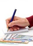 Hand, Feder, Notizbuch und Geld Lizenzfreie Stockfotos