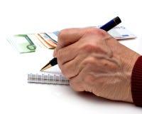 Hand, Feder, Notizbuch und Geld Stockfotografie