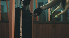 Hand of female changing weight at sports equipment, exercising in the gym stock video