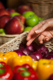 Hand of female costumer selecting vegetables from wicker basket. In organic section stock photo