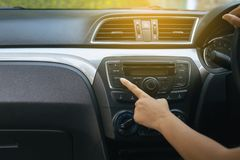 Hand of female driver turning on car radio system,Button on dashboard in car panel. Hand of female driver turning on car radio system,Button on dashboard in new stock image