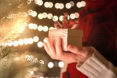 Hand of female holding Christmas gift box on bokeh lights background.  Royalty Free Stock Image