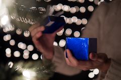 Hand female open blue Christmas gift box with bokeh lights background.  Stock Images