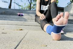 Hand female using elastic bandage with legs,Female putting bandage on her injured foot from sport royalty free stock photos