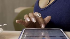 Hand of female, who is typing messeges on her tablet in the cafe, close up. Woman in blue top sits at the wooden table with brand new device on and writing by stock footage