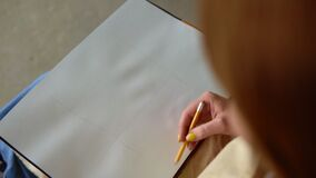 Hand of female with yellow manicure drawing at paper in her studio. Woman`s hand draws. Designer clothes or tailor