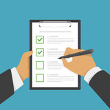 Hand filing checklist on clipboard. Stock Photography