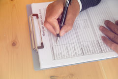 hand fill out mortgage loan application on a clipboard. A form t Royalty Free Stock Photography
