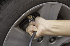Hand filling air into a car tire, close up Stock Photo