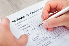 Hand filling application for employment Stock Photos