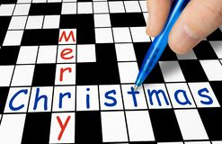 Hand filling in crossword - Merry Christmas. Holiday concept royalty free stock image