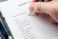 Hand filling in empty medical questionnaire Stock Images