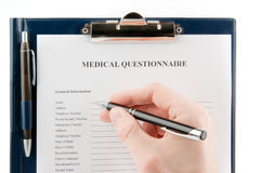 Hand filling in empty medical questionnaire Stock Photo