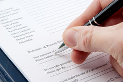 Hand filling in empty medical questionnaire Royalty Free Stock Images