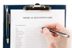 Hand filling in empty medical questionnaire Stock Image