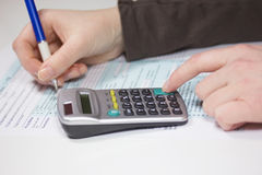 Filling income tax forms with calculator and pen Royalty Free Stock Photos