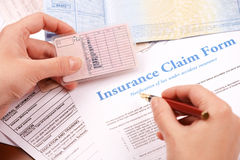 Hand filling in insurance claim form Stock Images