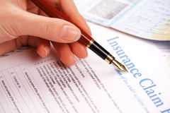 Hand filling in insurance claim form Royalty Free Stock Photo