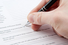 Hand filling in medical questionnaire form Royalty Free Stock Photos