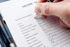 Hand filling in medical questionnaire form Stock Photo