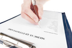 Hand filling in medical questionnaire form Stock Images