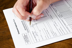 Hand filling out employment application Stock Photo