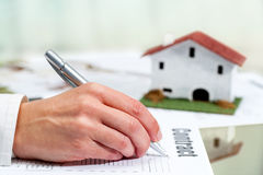 Hand filling out house buying contract. Royalty Free Stock Photo