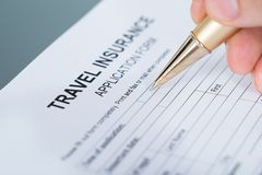 Hand filling travel insurance Royalty Free Stock Images