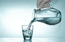 Filling the glass from a pitcher with water. Hand fills a glass with water from a glass pitcher Stock Images