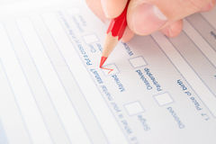 Hand fills questionnaire a red pencil stock image