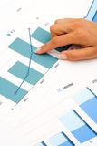 Hand on financial graphics. Close up of female hand on financial graphics Royalty Free Stock Image