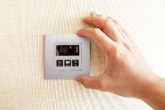 Hand with finger on air conditioner switch control Stock Photo