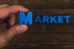 Hand and finger arrange text letters of MARKET word on wood table, with copy space for add advertising word or product. business. And finance concept idea stock photos