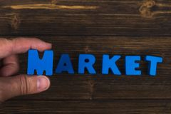 Hand and finger arrange text letters of MARKET word on wood table, with copy space for add advertising word or product. business. And finance concept idea stock images