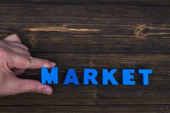 Hand and finger arrange text letters of MARKET word on wood table, with copy space for add advertising word or product. business. And finance concept idea royalty free stock images