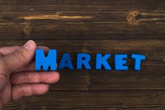Hand and finger arrange text letters of MARKET word on wood table, with copy space for add advertising word or product. business. And finance concept idea stock image