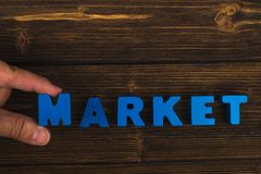 Hand and finger arrange text letters of MARKET word on wood table, with copy space for add advertising word or product. business. And finance concept idea royalty free stock photography