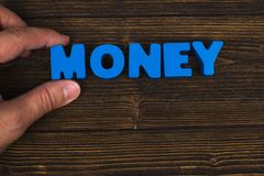 Hand and finger arrange text letters of MONEY word on wood table Royalty Free Stock Photo
