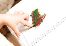 Hand finger paints. Hand of a little child draws a finger paints Royalty Free Stock Images