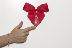 Hand with finger pointing under a red ribbon Royalty Free Stock Images