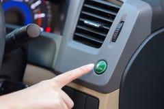 Hand finger press button eco mode inside car. Stock Photo
